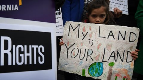 """Maya Casillas, 7, joins migrant rights group during a vigil to protest against US President Donald Trump's new crackdown on """"sanctuary cities"""", outside the City Hall in Los Angeles on January 25, 2017. Some 300 such cities, counties or states -- from New York to Los Angeles -- exist throughout the United States, and many of them have vowed since Trump's election to protect the estimated 11 million undocumented migrants living in the country.  / AFP / Mark RALSTON        (Photo credit should read MARK RALSTON/AFP/Getty Images)"""