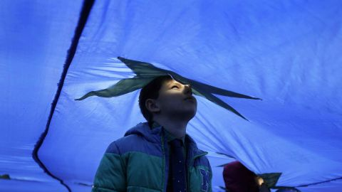 A child peers through a wind vent in a huge European Union flag during a March 25 event marking 60 years since the founding of the alliance.