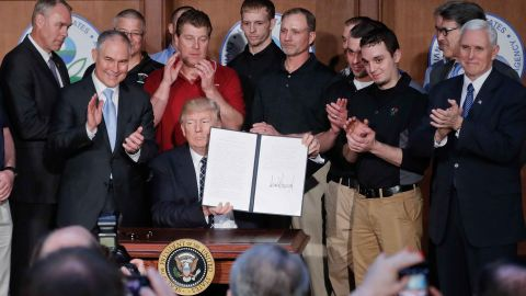 President Donald Trump, accompanied by coal miners and, from left, Interior Secretary Ryan Zinke, Environmental Protection Agency (EPA) Administrator Scott Pruitt, second from right, Energy Secretary Rick Perry, and Vice President Mike Pence, far right, holds up the signed Energy Independence Executive Order, Tuesday, March 28, 2017, at EPA headquarters in Washington. (AP Photo/Pablo Martinez Monsivais)