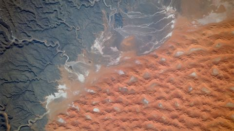 """The Tifernine dunes of east-central Algeria are pictured in this image, captured in 1995. """"The dunes lie in a basin of dark-colored rocks heavily cut by winding stream courses (top right),"""" explains the caption in the Nasa Image and Video Gallery. """"Very occasional storms allow the streams to erode the dark rocks and transport the sediment to the basin. Winds then mold the stream sediments into the complex dune shapes so well displayed here."""""""