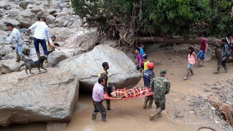 Volunteers and soldiers carry one of the injured in Mocoa.
