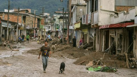 A man and a dog walk down a mud-filled street in Mocoa.