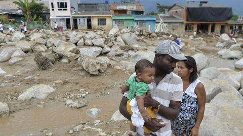 A man holds his son as he stands amid the remains of Mocoa.