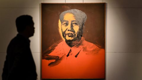 """A man walks past Mao by US artist Andy Warhol, 1973, an acrylic and silkscreen ink on canvas, during a pre-auction preview by Sotheby's in Hong Kong on March 17, 2017. An Andy Warhol portrait of former Chinese leader Mao Zedong will be auctioned in Hong Kong in a landmark sale that could fetch 15 million USD -- but mainland buyers may be wary of putting in a bid. The classic 1973 screen print by the legendary US pop artist will go under the hammer at Sotheby's next month with the highest estimate the auction house has ever seen for a painting in Asia. It comes as demand grows in the region for a wider variety of works, driven by appetite in China. The auction house describes the event as the first """"significant"""" sale of Western contemporary art in Hong Kong. / AFP PHOTO / Anthony WALLACE / RESTRICTED TO EDITORIAL USE - MANDATORY MENTION OF THE ARTIST UPON PUBLICATION - TO ILLUSTRATE THE EVENT AS SPECIFIED IN THE CAPTION        (Photo credit should read ANTHONY WALLACE/AFP/Getty Images)"""