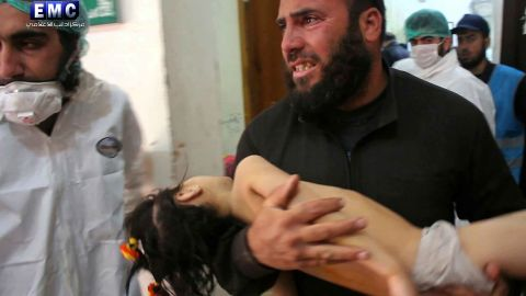 """A man carries a child at a makeshift hospital in Khan Sheikhoun. Activists have blamed the Syrian regime for the attack. In an apparent reference to the attack, two state-run Syrian media outlets reported that there was an explosion at a """"rebel poison gas factory"""" in the countryside of Idlib province. The government has denied using chemical weapons in the past."""