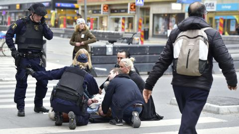 Police attend to people wounded in the Stockholm attack.