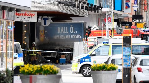 Emergency services work at the scene where a truck crashed into the Ahlens department store in central Stockholm on April 7. the truck hit pedestrians before it struck the store; four peole were killed, authorities said.