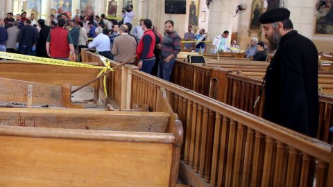A priest looks at the damage inside the church.