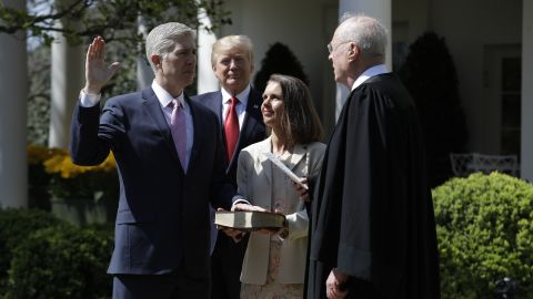 President Donald Trump watches as Supreme Court Justice Anthony Kennedy administers the judicial oath to Neil Gorsuch during a re-enactment in the Rose Garden of the White House on April 10, 2017. Holding the bible is Gorsuch's wife Marie Louise Gorsuch.