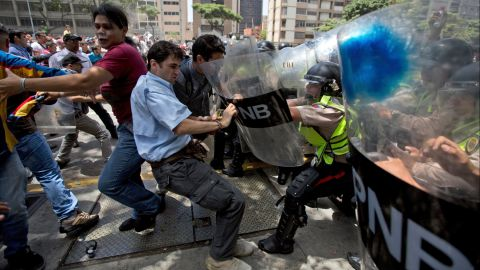 Demonstrators fight with national police officers in Caracas on Tuesday, April 4.