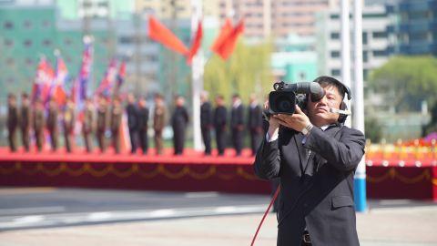 A North Korean cameraman films foreign journalists.