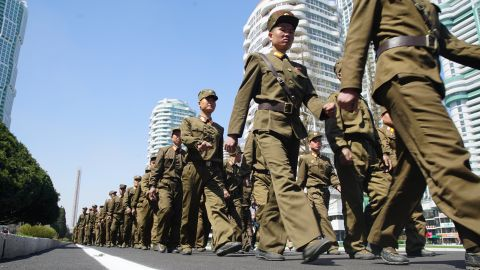 Soldiers march down the street.