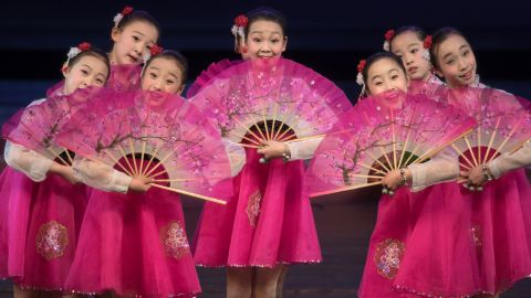 Children with fans entertain foreign journalists.