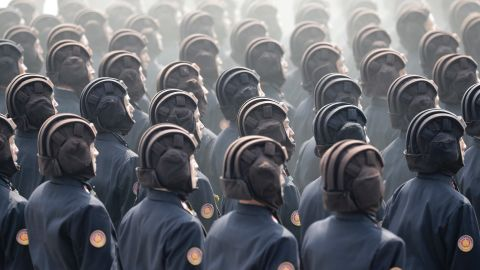 Helmeted servicemen march during the parade.