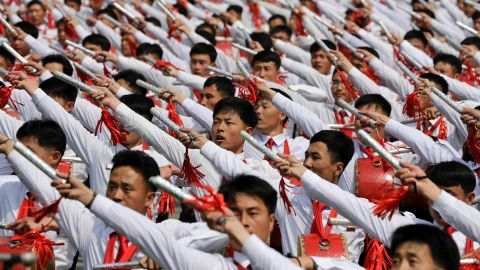 North Korean men beat drums as they parade across the square.