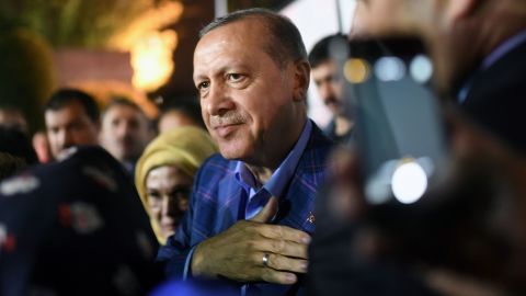 """Turkish president Recep Tayyip Erdogan (C), flanked by his wife Emine Erdogan (rear L), acknowledges supporters, during a rally, as he leaves after delivering a speech at the conservative Justice and Development Party (AKP) headquarters in Istanbul, on April 16, 2017, following the results of a nationwide referendum that will determine Turkey's future destiny. Erdogan on April 16, 2017 hailed Turkey for making a """"historic decision"""" as he claimed victory in the referendum on a new constitution expanding his powers. The """"Yes"""" campaign to give Turkish President expanded powers won with 51.3 percent of the vote a tightly-contested referendum although the """"No"""" camp had closed the gap, according to initial results. But Turkey's two main opposition parties said they would challenge the results. / AFP PHOTO / Bulent Kilic        (Photo credit should read BULENT KILIC/AFP/Getty Images)"""