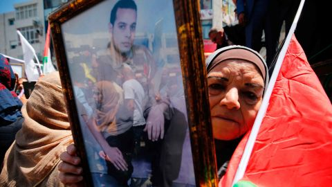 A woman holds the portrait of a Palestinian prisoner during a rally in Ramallah Monday.