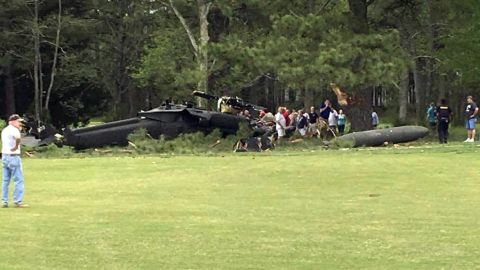 People examine an Army UH-60 helicopter from Fort Belvoir, Va., after it crashed at the Breton Bay Golf and Country Club after Monday, April 17, 2017, in Leonardtown, Md. (Rebecca Updegrave Cline via AP)