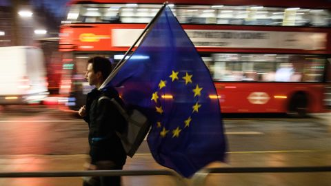 A man carries a European Union flag outside the Supreme Court in Parliament Square, London.