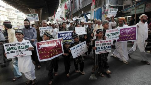 Indian Muslim children hold placards in English, Urdu and Hindi, as they march with activists to mark the 18th anniversary of the Babri Masjid Mosque demolition in Mumbai, India, Monday, December 6, 2010.