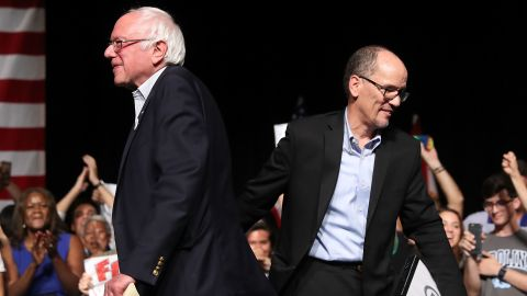 """MIAMI, FL - APRIL 19:  Sen. Bernie Sanders (I-VT) and DNC Chair Tom Perez walk past each other as Sen. Sanders takes to the stage to speak during their """"Come Together and Fight Back"""" tour at the James L Knight Center on April 19, 2017 in Miami, Florida. Sanders and Perez spoke on topics from raising the minimum wage to $15 an hour, pay equity for women, rebuilding the crumbling infrastructure, combatting climate change, making public colleges and universities tuition-free, criminal justice reform, comprehensive immigration reform and tax reform which demands that the wealthy and large corporations start paying their fair share of taxes. (Photo by Joe Raedle/Getty Images)"""