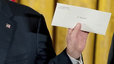 """Trump holds up a letter Sunday, January 22, that was left for him by former President Barack Obama. """"I just went to the Oval Office and found this beautiful letter from President Obama. It was really very nice of him to do that. And I will cherish that,"""" said Trump, <a href=""""http://www.cnn.com/2017/03/04/politics/donald-trump-obama-quotes/"""" target=""""_blank"""">who frequently criticized Obama</a> on the campaign trail. Trump wouldn't tell the press what was in the letter."""