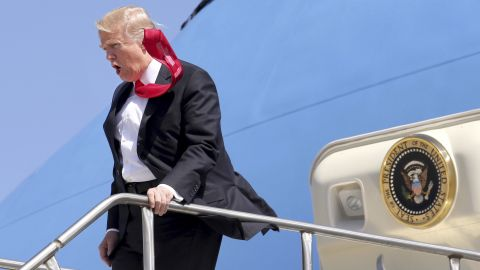 """A strong wind blows Trump's tie as he arrives at Orlando International Airport on March 3. <a href=""""http://www.cnn.com/videos/politics/2017/02/02/trump-tie-too-long-moos-pkg-erin.cnn"""" target=""""_blank"""">CNN's Jeanne Moos reports on Trump's presidential neckwear: Long ties with Scotch tape on the back</a>"""