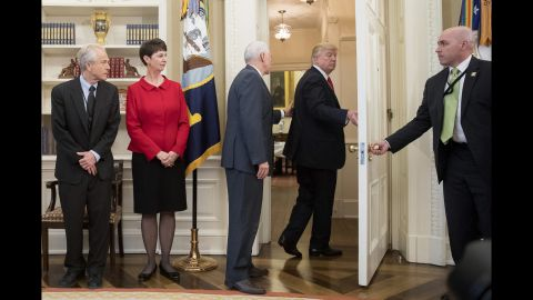 """Vice President Mike Pence, third from left, tries to stop Trump as Trump <a href=""""http://www.cnn.com/2017/03/31/politics/donald-trump-executive-order-signing-walk-out/index.html"""" target=""""_blank"""">walks out of an executive order signing ceremony</a> on Friday, March 31. During the signing ceremony, White House pool reporters asked Trump questions about former national security adviser Michael Flynn, who has offered to testify on Russian involvement in the US election. The President ignored the questions and moved to another room to sign the two executive orders, which regarded trade policy."""