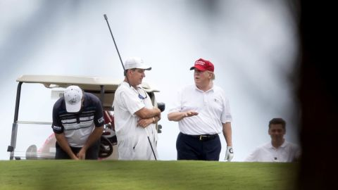 """Trump talks to a caddie during a round of golf in West Palm Beach, Florida, on Saturday, April 8. Trump frequently criticized President Obama for playing golf, <a href=""""http://www.cnn.com/2017/03/19/politics/trump-golf-weekends/"""" target=""""_blank"""">but he has been a frequent golfer</a> during his first few months in office."""