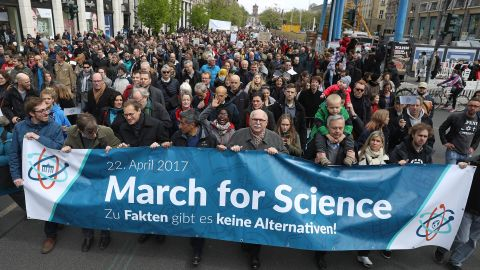 """People show support of scientific research in Berlin, Germany, residents march behind a sign that reads, """"There are no alternatives to facts."""""""
