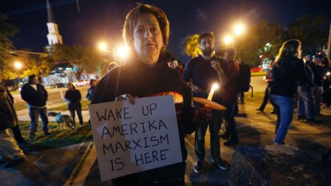 Dana Farley of New Orleans joins a candlelight vigil April 24 at the statue of Jefferson Davis.