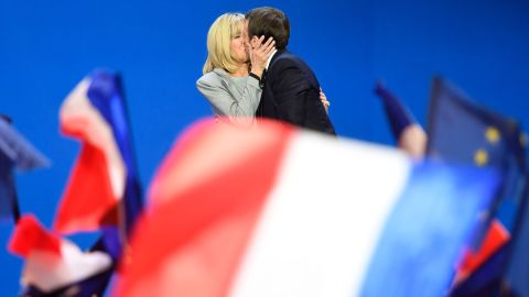 TOPSHOT - French presidential election candidate for the En Marche ! movement Emmanuel Macron kisses his wife Brigitte Trogneux (L) on stage at the Parc des Expositions in Paris, on April 23, 2017, after the first round of the Presidential election. / AFP PHOTO / Eric FEFERBERG / ALTERNATIVE CROP         (Photo credit should read ERIC FEFERBERG/AFP/Getty Images)