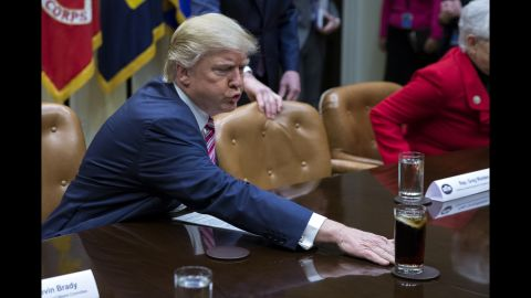 """Trump moves a drink across the table before a White House discussion about health care on Friday, March 10. The President's habit of moving things caught the eye of CNN's Jeanne Moos, <a href=""""http://www.cnn.com/videos/politics/2017/03/31/trump-moves-things-habit-pyschology-moos-dnt-erin.cnn"""" target=""""_blank"""">who reported on the unusual quirk.</a>"""