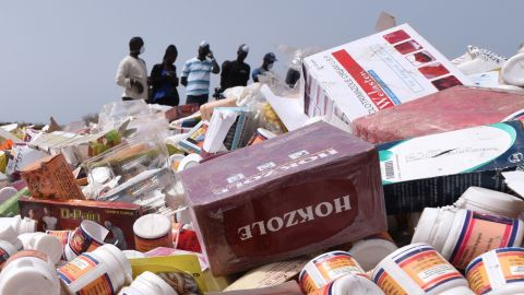 """People work to destroy, on April 21, 2015 at the Champ de tir des Mamelles in Dakar, about 4 tonnes of counterfeit and illegal medicine seized in an operation as part of the fight against pharmaceutical crime, called """"Porc-Epic"""" (porcupine). The operation was initiated simultaneously in ten other countries in the sub-region over three days (May 27, 28 and 29, 2014), in collaboration with Senegal's Directorate of Pharmacy and Medicine and Senegal's College of Pharmacists. AFP PHOTO / SEYLLOU        (Photo credit should read SEYLLOU/AFP/Getty Images)"""