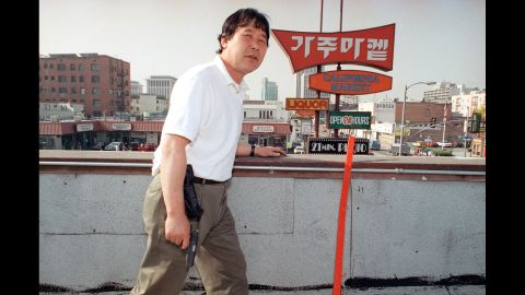 Store owner Richard Rhee stands vigil, armed with a handgun and a cellular phone on the roof of his grocery store in the Koreatown area of Los Angeles on May 2, 1992.