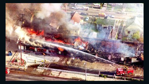 A fire department crew sprays water on a burning mini-mall in south Los Angeles on April 30,1992 after a night of rioting.