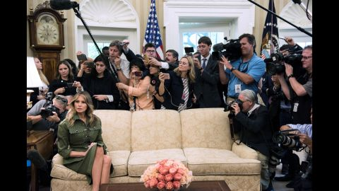 Trump listens while her husband speaks to the press in the White House Oval Office.