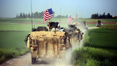 TOPSHOT - US forces, accompanied by Kurdish People's Protection Units (YPG) fighters, drive their armoured vehicles near the northern Syrian village of Darbasiyah, on the border with Turkey on April 28, 2017. / AFP PHOTO / DELIL SOULEIMAN        (Photo credit should read DELIL SOULEIMAN/AFP/Getty Images)