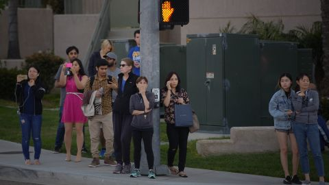 A crowd gathers outside the La Jolla Crossroads apartments in San Diego.
