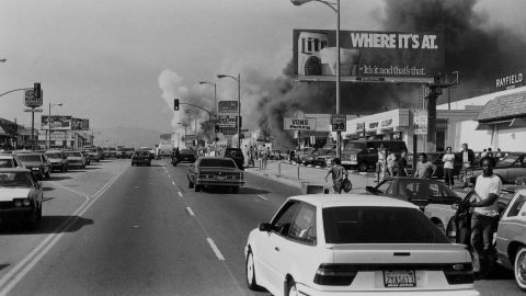 """Buildings going up in smoke on an unidentified street during the riots of 1992, following the decision in the Rodney King case. Film still from """"LA 92."""""""