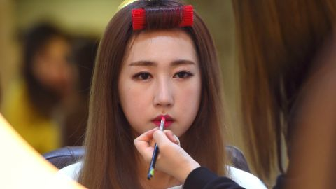 This picture taken on March 16, 2017 shows Lee So-Young (Seul-Bee), a member of K-pop group SixBomb, having her make-up done at a beauty parlour in Seoul. All four members of obscure K-pop outfit SixBomb went through extensive plastic surgery, from nose jobs to breast implants, before releasing their new single on March 16. / AFP PHOTO / JUNG Yeon-Je / TO GO WITH SKorea-social-music-lifestyle, FEATURE by Jung Ha-Won          (Photo credit should read JUNG YEON-JE/AFP/Getty Images)