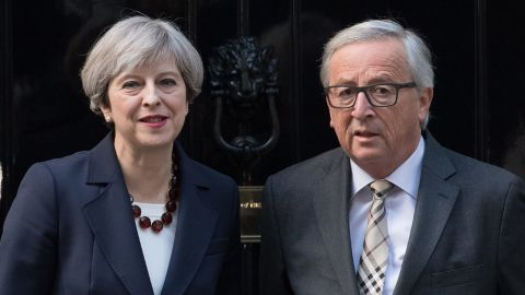 Theresa May stands with European Commission president, Jean-Claude Juncker at the front door of 10 Downing Street in London.