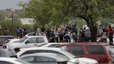 Students gather outside a building at North Lake College in Irving, Texas, after a shooting.