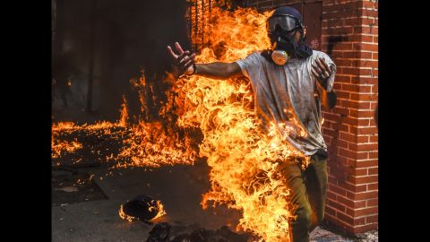 A demonstrator catches fire during protests in Caracas on May 3. It happened as protesters clashed with police and the gas tank of a police motorcycle exploded. Other photos from the scene showed the man being attended for burns to his body.