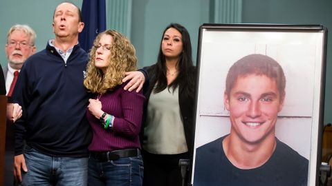 Jim and Evelyn Piazza stand by as Centre County District Attorney Stacy Parks Miller announces the results of an investigation into the death of their son Timothy Piazza, seen in photo at right, a Penn State University fraternity pledge, during a press conference Friday, May 5, 2017, in Bellefonte, Pa. Timothy Piazza had toxic levels of alcohol in his body and was badly injured in a series of falls, authorities said Friday in announcing criminal charges against members of the organization and the frat itself. (Joe Hermitt /PennLive.com via AP)