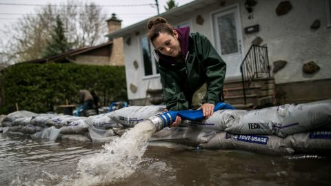 A resident of Mercier Island drains her house of floodwaters.