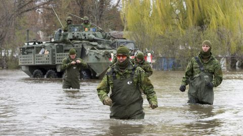 Canadian armed forces wade through flooded streets as they provide assistance in Deux-Montagnes, Quebec, on May 8.