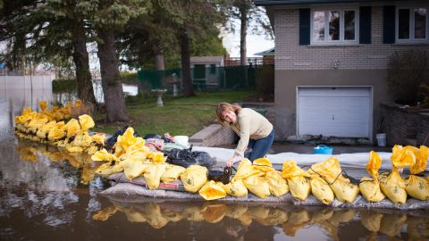 Johanne Aubin uses a pool pump to protect her Montreal home from floodwaters on May 8.