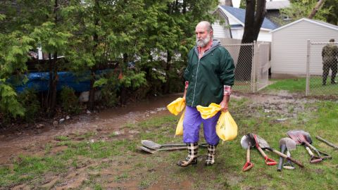 A man in Montreal carries sandbags on Sunday, May 7.