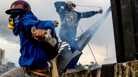 Opposition activists clash with riot police in Caracas on Monday, May 8.